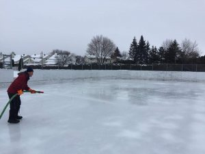 Photo of volunteer flooding the rink
