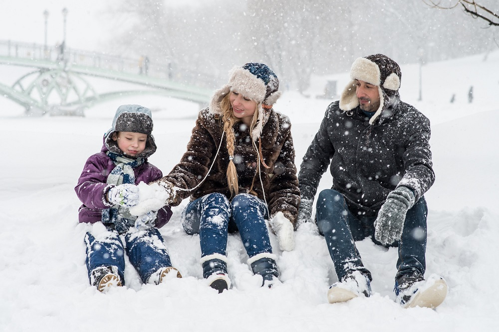 image f a man, a woman and a child sitting in the snow