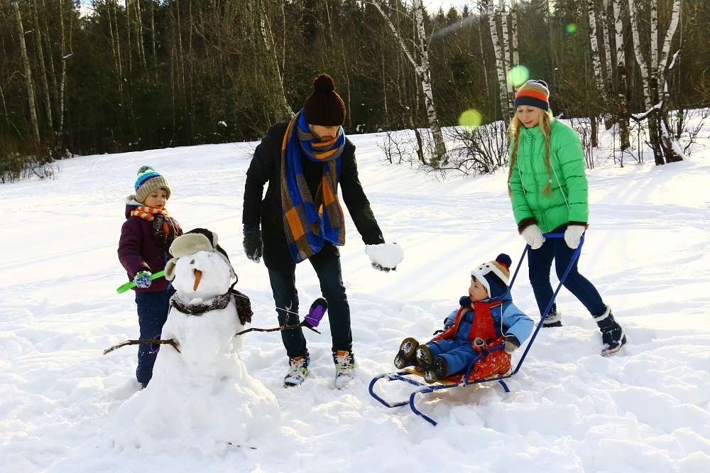 image of family playing in the snow with a sled and making a snowman