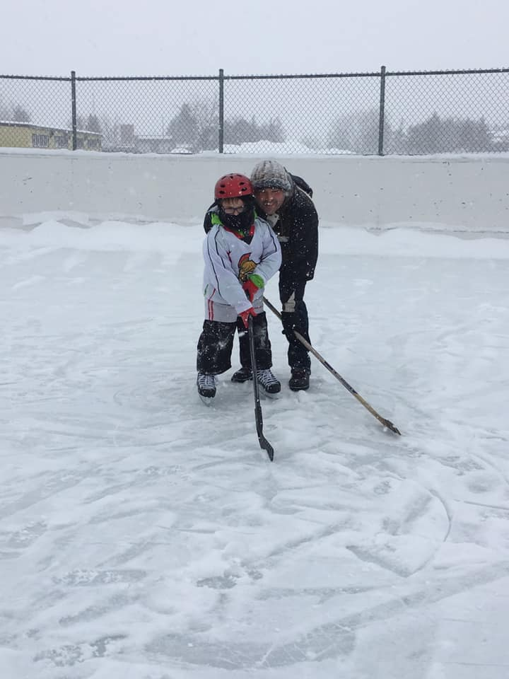image of father and son on the community rink with hockey sticks at the Carnival