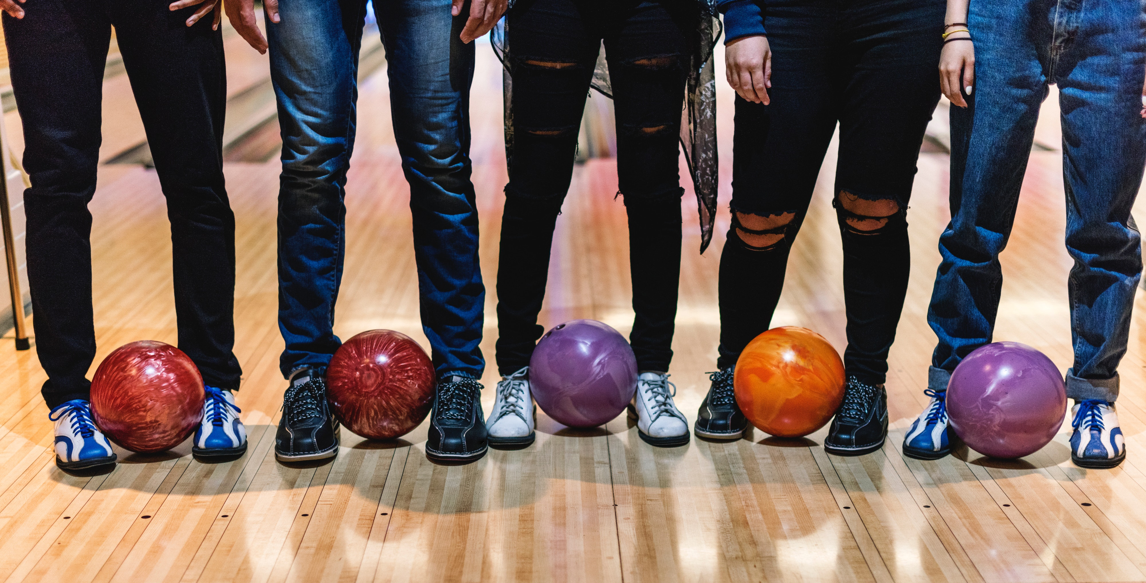 image of 5 people (legs only) standing with a bowling ball between their feet