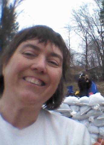 photo of Louise in front of a wall of sandbags