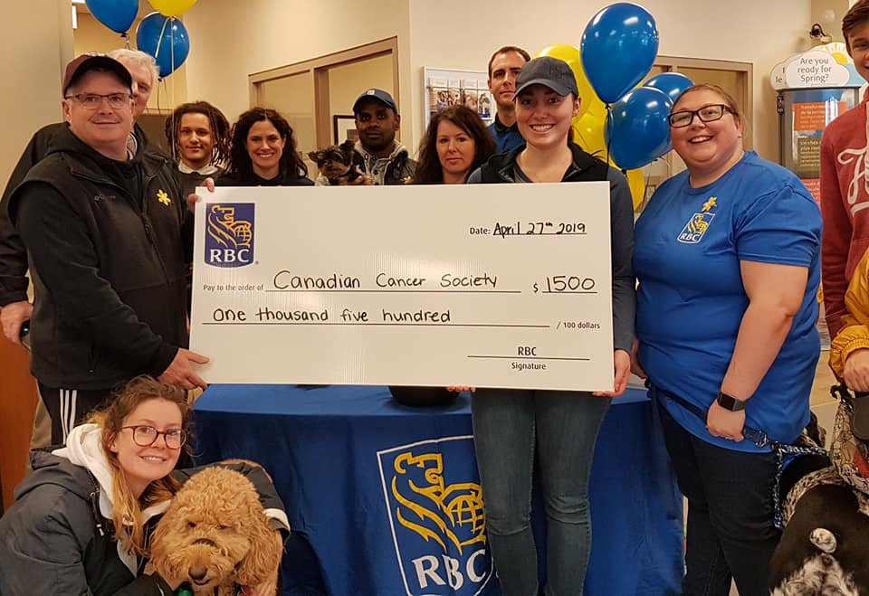 group photo of RBC staff and community members with large cheque  showing the approximate total raised ($1500).