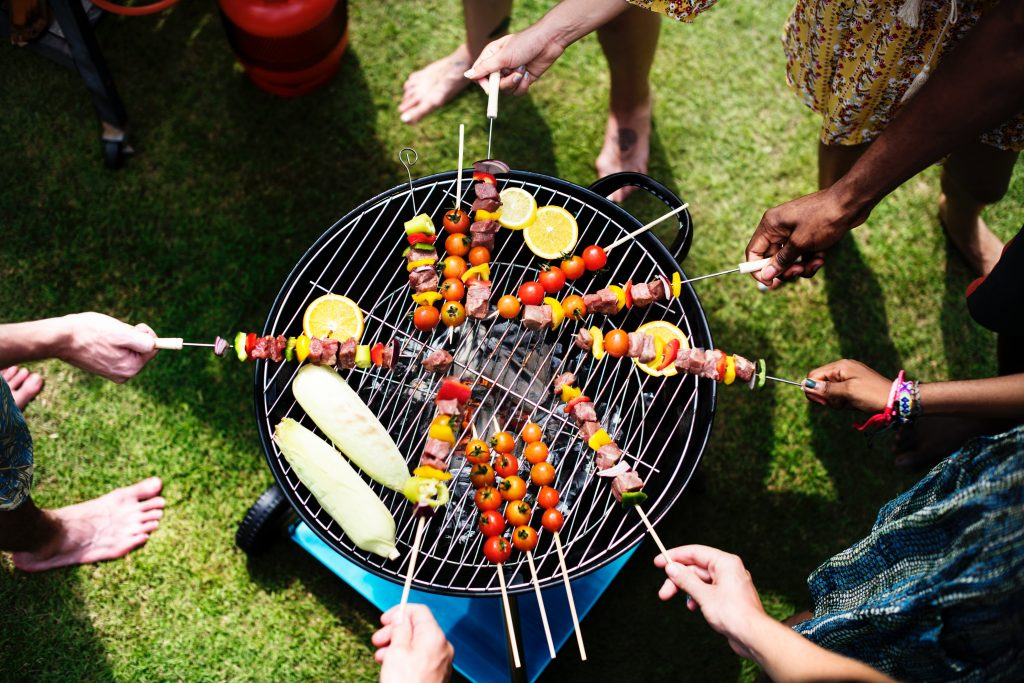 several people standing around a BBQ with skewers on the BBQ