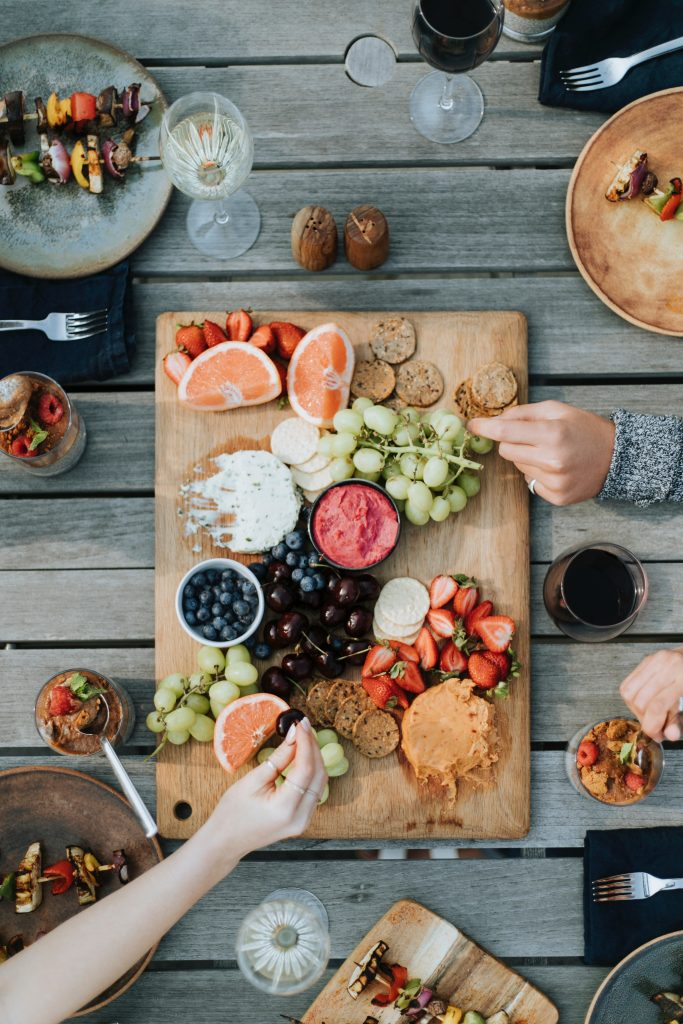 photo of table with a spread of food and hands reaching for food.