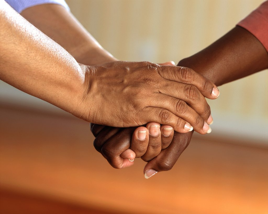 image of two sets of hands clasped