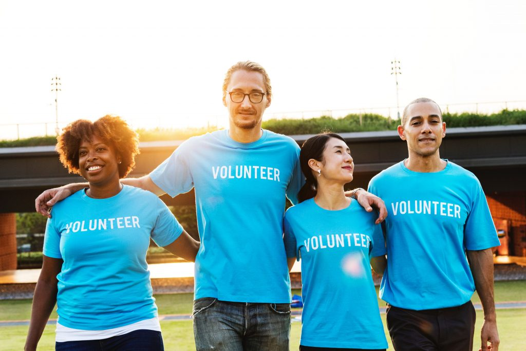 "4 people standing with their arms around one another, all wearing blue t-shirts that say ""volunteer"""