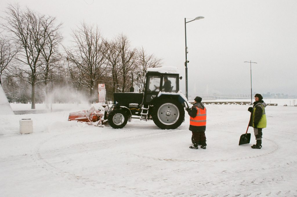a snow removal tractor in a parking lot with two people holding shovels standing nearby