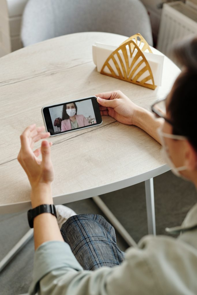 man wearing a mask and having a video call with a woman wearing a mask