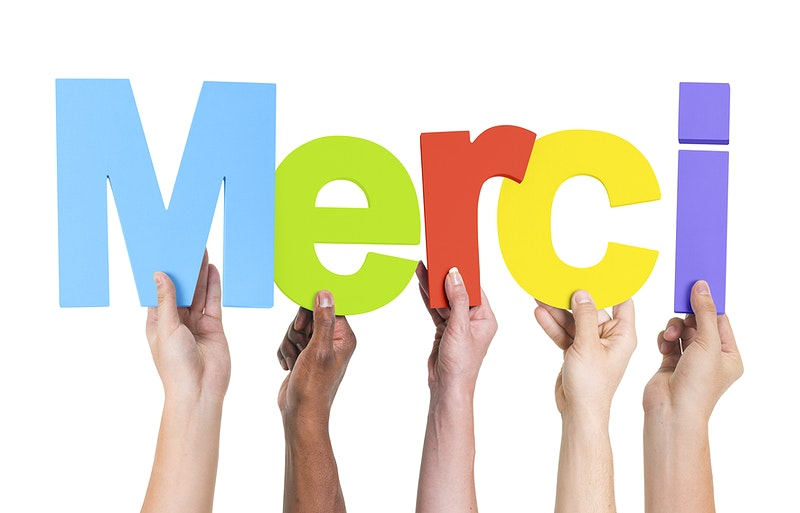 people holding up letters that spell MERCI