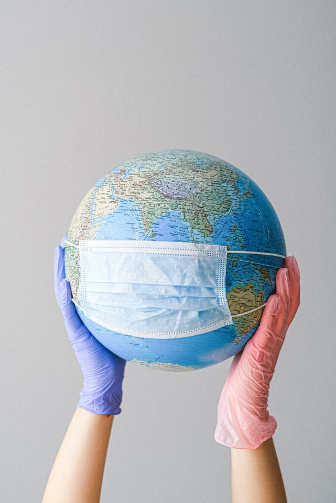 gloved hands holding a globe, the globe is wearing a mask