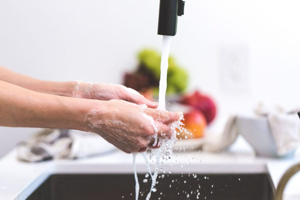 person washing their hands at the kitchen sink
