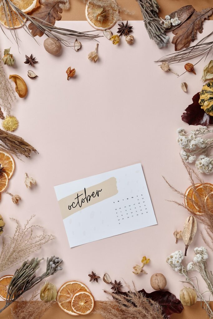 decorative image - dried herbs and flowers along the border with an October calendar centered in the shot.