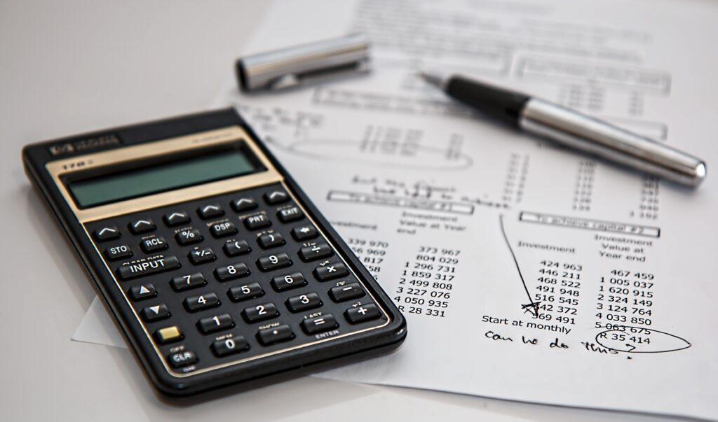 image of a calculator, a pen and a print out of a budget